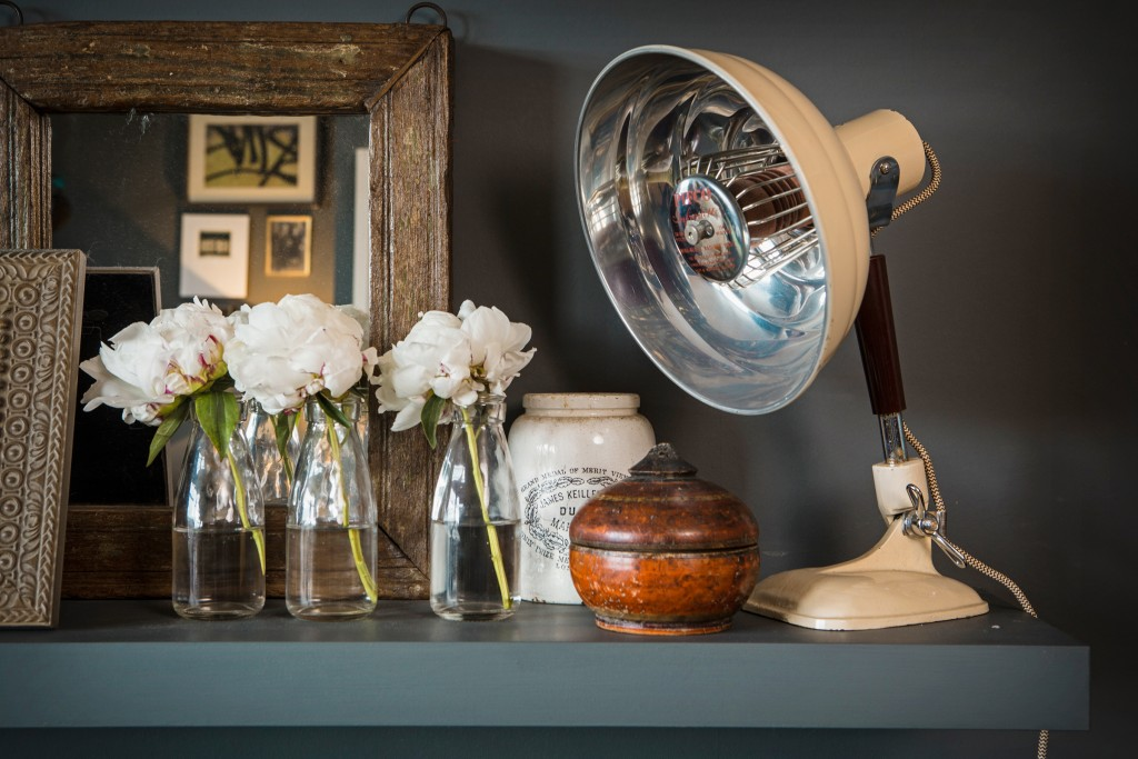 Sooz's eclectic mantlepiece shows a wide variety of styles and eras. A vintage medical lamp sits next to an old India spice pot, vintage marmalade jar and fresh white flowers in old milk bottles and a wonderfuuly textured antique mirror.