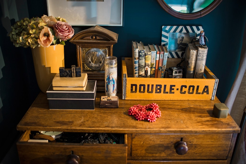 Sooz has used a colourful industrial vintage soda crate, on top of an antique oak chest of drawers to store old books, while the top shows small jewellery boxes, an old old and comtemporary photo frames, vase and flowers.