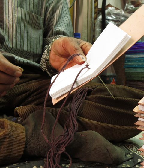 Step 5 - Binding The Journal. Hitesh uses the common deep stitch method to bind the journal using a 5 inch needle and hessian or leather string.