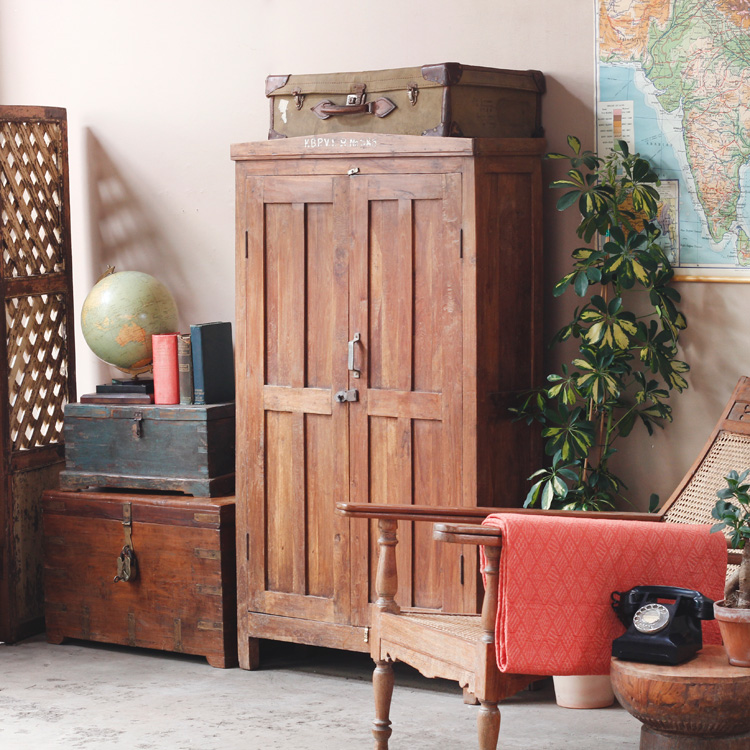 A solid teak antique armoire used in a sitting room as a cupboard for displaying books and collections