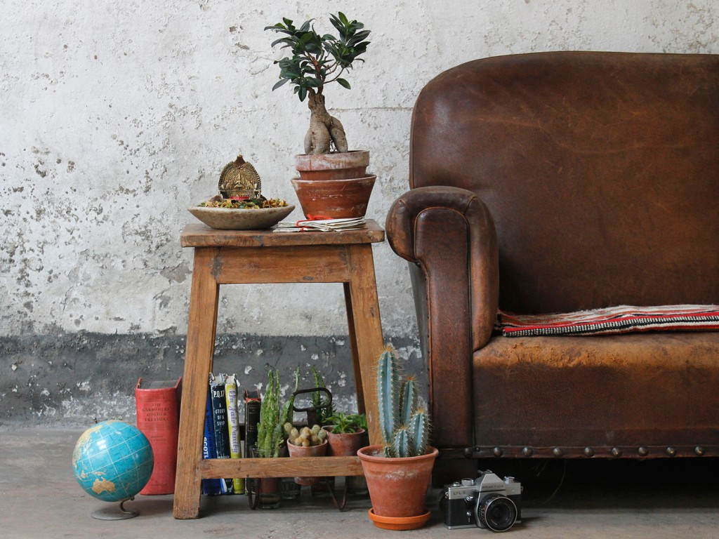 A vintage school stool used as a side table